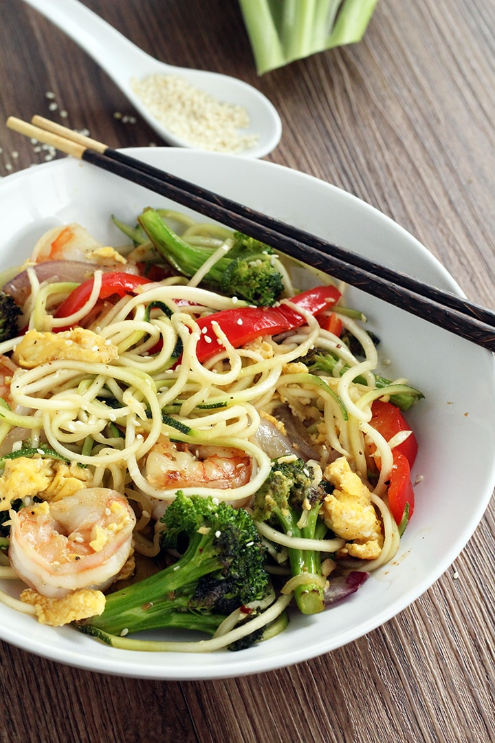 "olive oil cooking spray 3/4 cup broccoli florets (about 5)  1 egg, beaten 3 tsp sesame oil  1/2 tsp freshly minced ginger 1 tsp minced garlic 1/2 red onion, sliced lengthwise into 1/2-inch thick ""strips"" (fajita-style) 1 small red bell pepper, sliced into 1/2-inch thick ""strips"" (fajita-style) salt and pepper, to taste 1/4 tsp (or one small pinch) of red pepper flakes 3 tbsp soy sauce 1 tsp honey 1 tsp rice vinegar 3-4 jump shrimp, defrosted, peeled and deveined 1/4 tsp white sesame seeds"