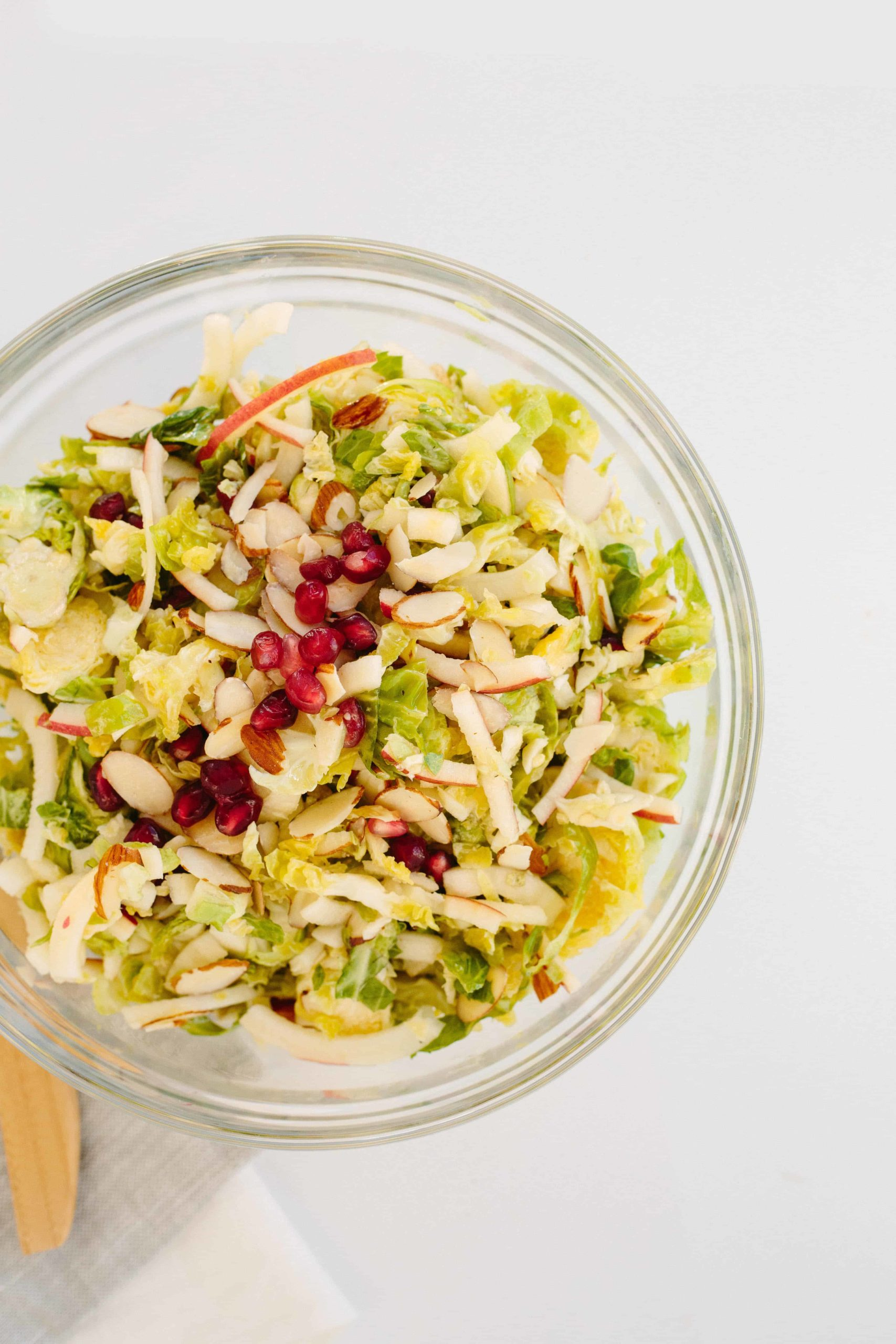 Shredded Brussels Sprouts and Spiralized Apple Slaw with Maple-Cider Dressing and Pomegranates